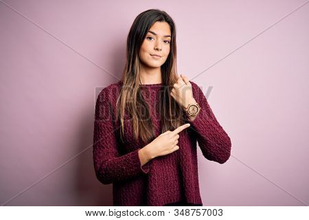 Young beautiful girl wearing casual sweater over isolated pink background In hurry pointing to watch time, impatience, looking at the camera with relaxed expression