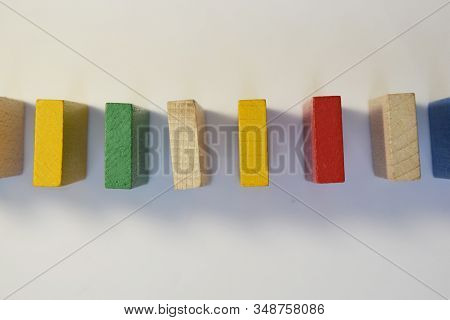 Colored, Multi-colored Dominoes Stand In A Row, Exactly. Chain Reaction Of Colorful Dominoes. The Vi