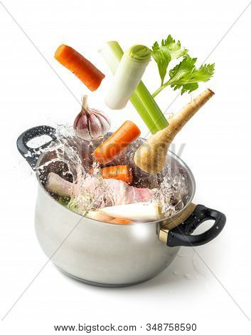 Boiling Vegetables Flying Towards The Pot With Splashing Water, On White Isolated Background