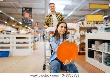 Couple jokes with cart and plate, houseware store
