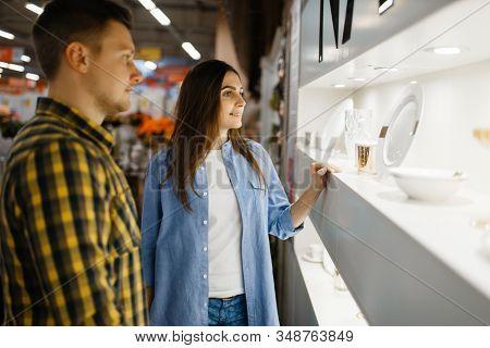Couple choosing wine glasses in houseware store