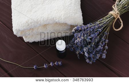 In A Dark Bottle Of Essential Oil And A Bunch Of Dry Lavender Next To A White Terry Towel.
