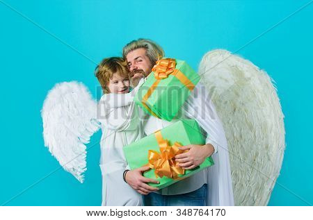 Happy Father In Angel Costume With Little Son Angel Holds Present. Cute Angel. Valentines Day. Fathe
