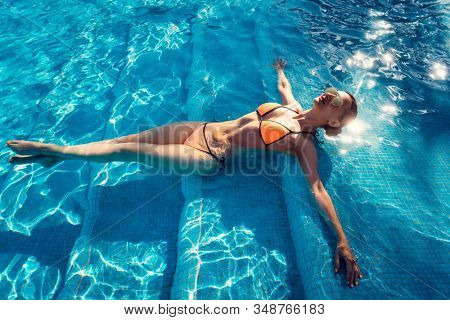 Beautiful woman relaxing in swimming pool of resort or hotel enjoying the water