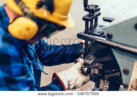 Worker does manual steel plate bevelling process in a factory, workshop. Also chamfering