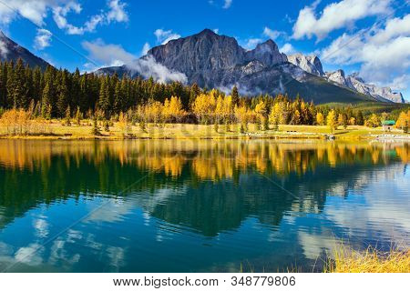 The Canadian Rockies. The city of Canmore in Banff Park. Bright autumn forest is reflected in the smooth water of the lake. The concept of active, ecological and photo tourism