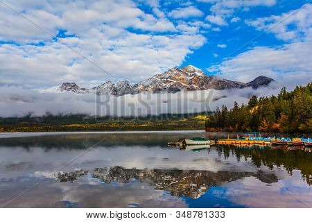 The morning mist rises beautifully. Pyramid Mountain is reflected in the smooth cold water of Pyramid Lake. Rocky Mountains, Canada. The concept of ecological and photo tourism