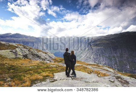 Couple Tourist Standing Against Amazing View, Beautiful Nature Landscape Hiking In Norway Trolltunga