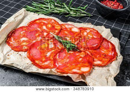 Sliced Chorizo Salami. Spanish Traditional Chorizo Sausage. Black Background. Top View