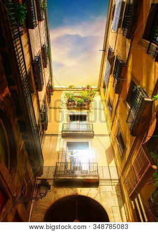 Passageway In The Narrow Streets Of Barcelona Near La Rambla Street Showing Window Glowing In Sunset