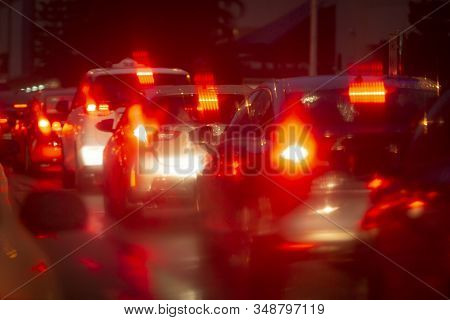 Cars In Night Traffic Jam With Abstract Bokeh Caused By Rain Drops Reflecting Onto Car Windscreen. R