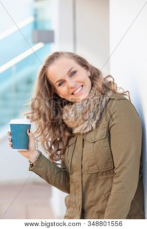 Happy smiling Woman with take away coffee in a break from work on the streets