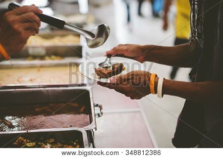 Volunteers Hand Over Delicious Food To Homeless People Who Are Starving And Need Food : Concept Of F