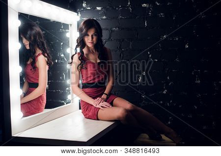 Sensual Woman In A Dark Room. Modern Loft Interior, And Stylish Make Up Table With Light Bulbs.