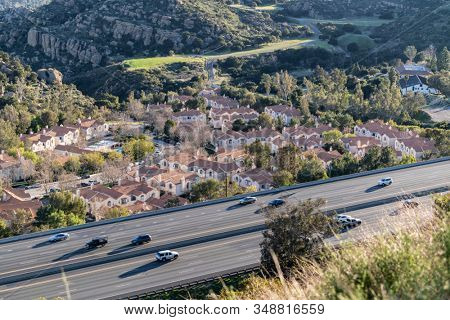 Freeway adjacent condos and traffic on route 118 through the Santa Susana Pass in scenic Chatsworth neighborhood of Los Angeles, California,