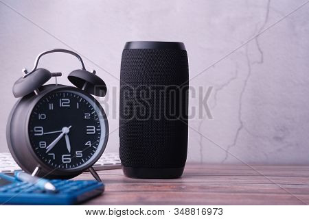 Smart Speaker With Clock On Table Against A Wall