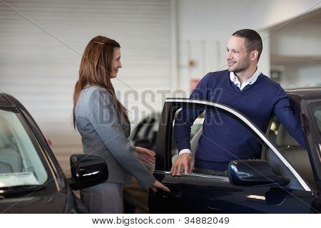 Woman opening car door  in a garage