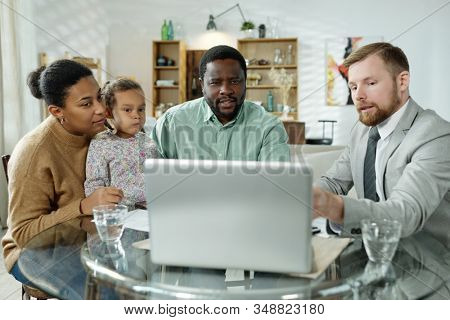 Bearded elegant adviser showing information to ethnic family while giving home loan consultation