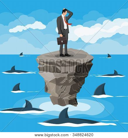 Worried Businessman On Tiny Island In Sea And Surrounded By Sharks. Desperate Business Man Against F