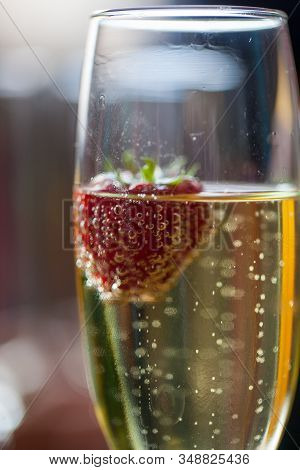 Glas Of Sparkling Wine Or Champagne And Strawberry On A Blurry Background During Some Sort Of Festiv