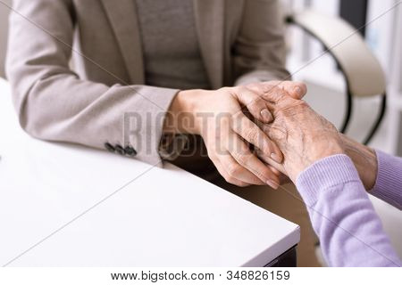 Close-up of unrecognizable social worker holding hands of elderly woman while supporting her