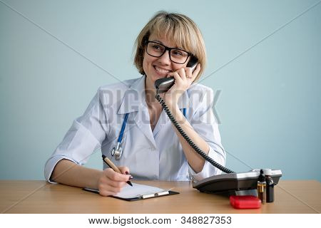 Happy Medical Worker Is Consulting A Patient By A Phone.