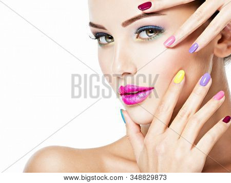 Close-up face of a beautiful woman  with multicolor nails and fashion makeup .