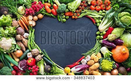 Panoramic colorful food background with assortment of fresh organic vegetables with copy space in heart shape