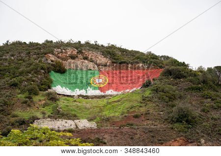 Alte, Portugal - January 24, 2020: Iconic Portugal Flag Painted On The Mountain Hillside Is A Landma