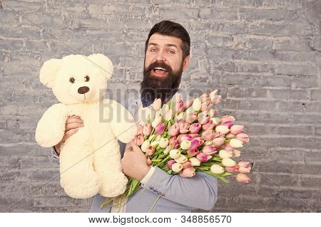 Waiting For Darling. Man Well Groomed Wear Tuxedo Bow Tie Hold Flowers Tulips Bouquet And Big Teddy