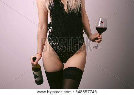 Sexy Young Woman In Erotic Black Lingerie With Glass Of Red Wine. Beautiful Nude Body Of Sensuality