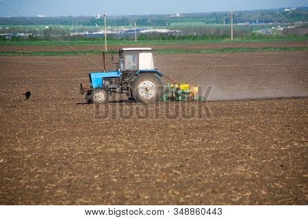 The Farmer On The Tractor With The Attached Mechanical Seeder Sows The Seeds On The Field