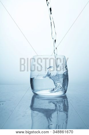 A Stream Of Water Flowing Into A Transparent Glass Cup With A Splash Of Drops And Drops. A Jet Of Cl