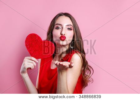 Sexy Woman Blowing A Kiss From Her Hand. Woman With Heart Shaped . Perfect Make Up With Red Lips. Se