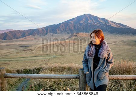 Lovely Cute Japanese Girl Standing On Aso Active Volcano Background With Smoke At Mount Aso, Kumamot