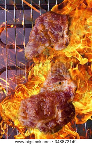 Raw Sliced ​​pork Neck On Grill. Flames Lick The Meat.raw Streaky Meat On Electric Grill.season Of G