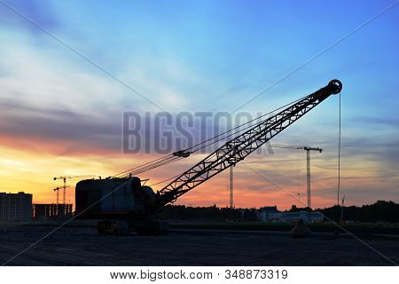 Large Crawler Crane Or Dragline Excavator With A Heavy Metal Wrecking Ball On Sunset Background. Wre