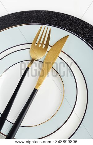 Close Up Side View Golden Fork And Knife On Plate. Golden And Black Silverware On Light Blue Plates