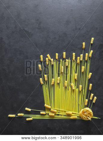 Pasta With Copy Space On The Black Table. Italian Pasta Spaghetti, Tagliatelle, Fusilli, Cavatappi O