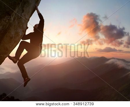 Rock Climbing. Young Male Risky Climber Trying Staying On Challenging Cliff Route. Scenic Mountain L