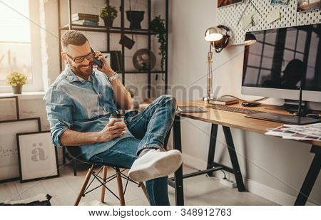 Young Handsome Business Man Freelancer Working At Home On A Computer