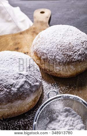 Donuts Covered With Powdered Sugar On The Wooden Cutting Board And Stony Worktop.