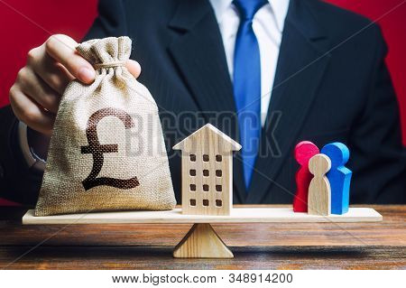 Man Puts Pound Sterling Money Bag And House On Scales With A Family. Assistance With Housing, Financ
