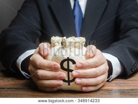 Businessman Hugs Us Dollar Money Bags. Bank Deposit. Budget Management, Tax Collection. Trade, Econo