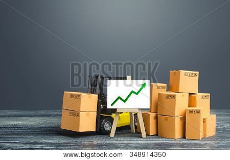 Forklift Near Boxes And Easel With Green Arrow Up. Growth Trade And Production Rates, Increased Sale