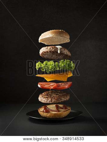 Maxi Hamburger With Flying Ingredients Placed On Black Background. Conceptual Jumping Burger. Delici