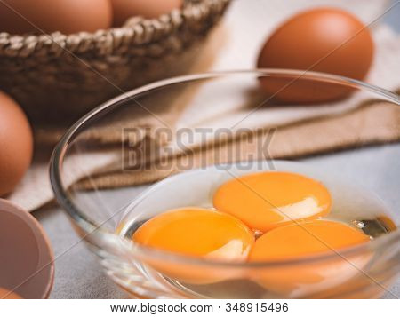 Close Up Image Of Three Eggs Yolk In Clear Bowl Are One Of The Food Ingredients On The Restaurant Ta