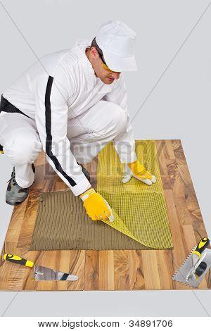 Applies Reinforce Fiber Mesh On Tile Adhesive On Wooden Floor