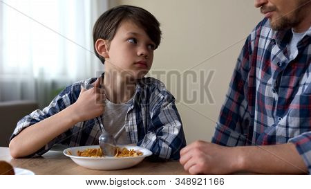 Little Sad Boy Mixing Cornflakes With Spoon, Looking At Father, Poor Appetite