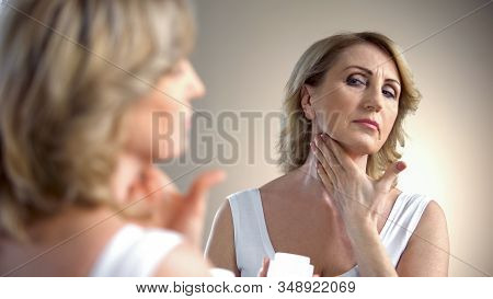 Elderly Lady Applying Anti-age Cream On Neck, Skin Care In Old Age, Wrinkles